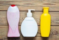 Botellas de productos para el cuarto de baño Riegue el gel, jabón líquido, champú en una tabla de madera Visión superior Fotos de archivo libres de regalías