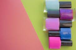 Botellas de pulimento de clavo Un grupo de manicuras brillantes en un rosa, fondo verde Con el espacio vacío a la izquierda foto de archivo libre de regalías