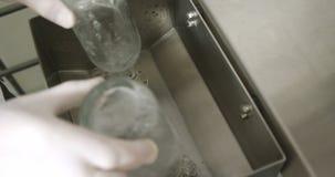 Botellas de relleno del trabajador de sexo masculino con el licor 4k metrajes