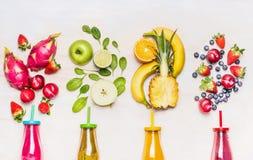 Botellas de smoothies de las frutas con los diversos ingredientes en el fondo de madera blanco, visión superior, cierre para arri Imagen de archivo libre de regalías