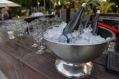 Botellas de vino blanco en el hielo y los vidrios vacíos próximos para el vino Imagen de archivo libre de regalías