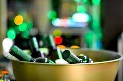 Botellas de vino cerradas en un cuenco de oro del hierro en un acontecimiento en un fondo defocused con las luces multicoloras imagen de archivo libre de regalías