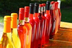 Botellas de vino coloridas en fila en una tabla de madera en el Sun Imagenes de archivo