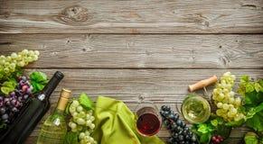 Botellas de vino con las uvas y corchos en fondo de madera Imagen de archivo libre de regalías