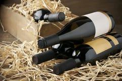 Botellas de vino en caja de madera y paja Imagen de archivo libre de regalías