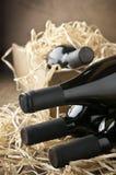 Botellas de vino en caja de madera y paja Imágenes de archivo libres de regalías