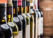 Botellas de vino en fila y barrilete del vino del roble foto de archivo