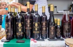 Botellas de vino de la zarzamora en venta en el mercado callejero en la ciudad de Rijeka imagen de archivo libre de regalías