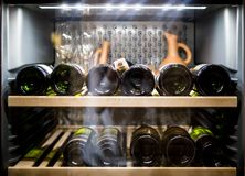 Botellas de vino que se refrescan en refrigerador imagen de archivo