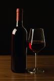 Botellas de vino rojo y silueta de cristal en la tabla de madera y el fondo negro Imagen de archivo libre de regalías