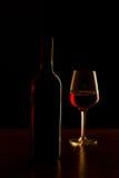 Botellas de vino rojo y silueta de cristal en la tabla de madera y el fondo negro Fotografía de archivo