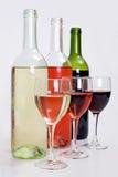 Botellas de vino rosado rojo, blanco y con los vidrios Foto de archivo