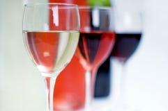 Botellas de vino rosado rojo, blanco y con los vidrios en frente Imágenes de archivo libres de regalías
