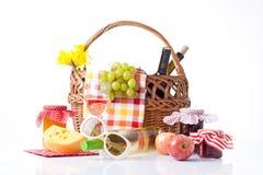 Botellas de vino y de cesta de la comida campestre con la comida deliciosa Fotos de archivo libres de regalías