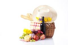 Botellas de vino y de cesta de la comida campestre con la comida deliciosa Fotos de archivo