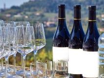 Botellas de vino y de vidrios con el campo de Langhe foto de archivo libre de regalías