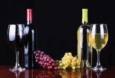 Botellas de vino y vidrios de vino sobre negro Fotografía de archivo