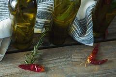 Botellas del aceite de oliva con herbario y las especias Fotos de archivo