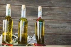 Botellas del aceite de oliva con herbario y las especias Imágenes de archivo libres de regalías