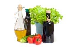 Botellas del aceite de oliva con la ensalada y las verduras Fotografía de archivo