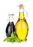 Botellas del aceite y del vinagre de oliva con albahaca Fotos de archivo