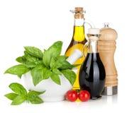 Botellas del aceite y del vinagre de oliva con albahaca y tomates Foto de archivo libre de regalías