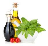 Botellas del aceite y del vinagre de oliva con albahaca y tomates Fotografía de archivo libre de regalías
