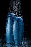 Botellas del champú y del gel en descensos descendentes del agua Imágenes de archivo libres de regalías