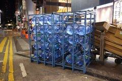 botellas del Cinco-galón de agua en la calle de la noche imagenes de archivo