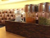 Botellas del condimento tales como sal, orégano, pimienta de cayena, p negro Imagen de archivo