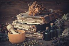 Botellas del tinte, manojos de las hierbas sanas, pila de libros antiguos, morteros, saco de hierbas medicinales El perforatum he fotografía de archivo