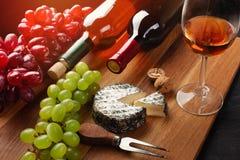 Botellas del vino blanco rojo y con el manojo de uvas, de cabeza del queso, de nueces y de copa en el tablero de madera y el fond imagen de archivo