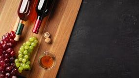 Botellas del vino blanco rojo y con el manojo de uvas, de nueces y de copa en el tablero de madera y el fondo negro imagenes de archivo