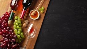 Botellas del vino blanco rojo y con el manojo de uvas, de queso, de miel, de nueces y de copa en el tablero de madera y el fondo  fotos de archivo