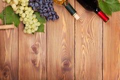 Botellas del vino blanco rojo y y manojo de uvas Imágenes de archivo libres de regalías