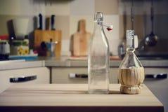 Botellas en la tabla de madera en fondo de la cocina Foto de archivo