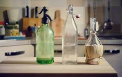 Botellas en la tabla de madera en fondo de la cocina Fotografía de archivo