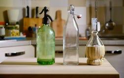 Botellas en la tabla de madera en fondo de la cocina Foto de archivo libre de regalías
