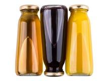 Botellas invertidas de mentira con los zumos de fruta en blanco Foto de archivo