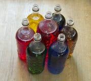 Botellas llenadas del líquido de diversos colores fotos de archivo