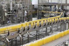 Botellas llenas que mueven encendido la banda transportadora en industria de embotellamiento Imágenes de archivo libres de regalías