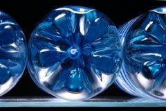 Botellas plásticas azules en estante del refrigerador Imagenes de archivo