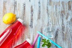 Botellas plásticas con las bayas, bebida de restauración cubos de hielo y pajas de beber dispersados en el fondo de un de madera  fotografía de archivo