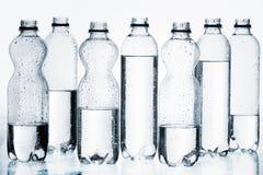 Botellas plásticas de agua en fila aislada Imágenes de archivo libres de regalías