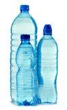 Botellas plásticas de agua mineral aisladas en blanco Foto de archivo