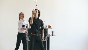 Botellas profesionales del hombre y de la mujer del camarero y cóctel de la sacudida que hacen juegos malabares en la tabla móvil almacen de video