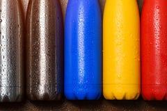 Botellas termas inoxidables coloridas, en una tabla de madera rociada con agua Botella, azul, amarillo y color rojos mates del pl fotos de archivo libres de regalías