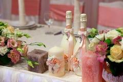 Botellas, velas y flores adornadas del champán en la tabla de la boda con las decoraciones Foto de archivo
