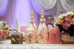 Botellas, velas y flores adornadas del champán en la tabla de la boda con las decoraciones Imagen de archivo libre de regalías