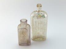 Botellas viejas de la medicina en el fondo blanco Imágenes de archivo libres de regalías
